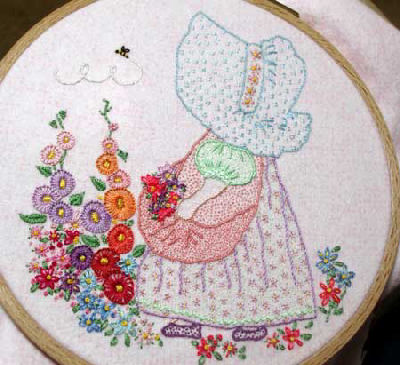 Embroidered quilt: sunbonnet girl in flower garden with bee