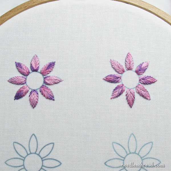 Two flowers stitched with variegated floss