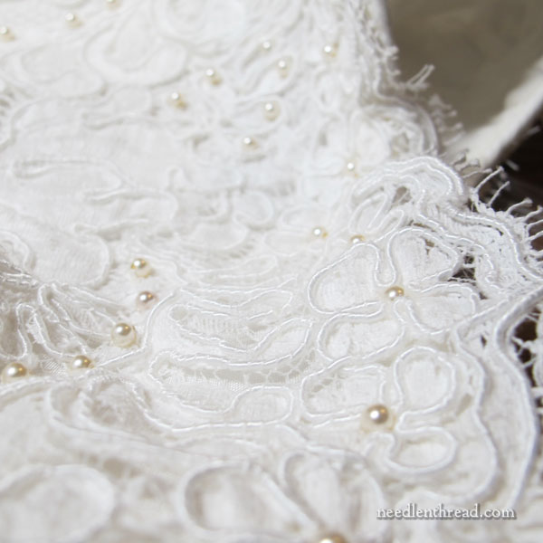 Hand beading a wedding gown with pearl beads